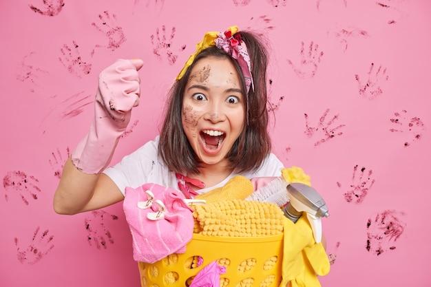 A dona de casa desarrumada exclama alto, fecha o punho e faz poses de limpeza da casa perto do cesto de roupa suja com o rosto sujo isolado sobre a parede rosa