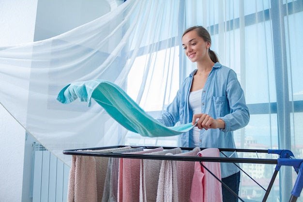 A dona de casa feliz pendura o linho molhado na secadora depois de lavar a roupa em casa. tarefas domésticas e tarefas domésticas
