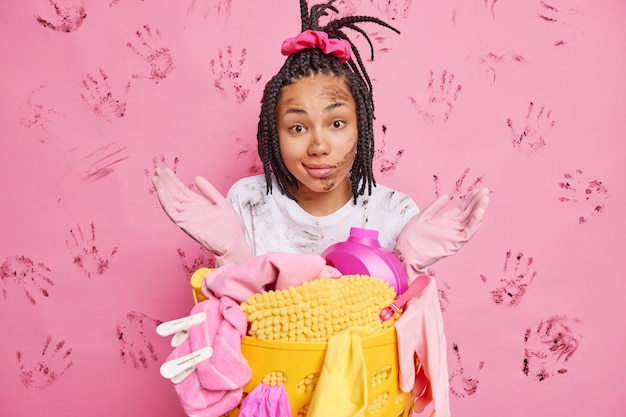 A dona de casa hesitante espalha as palmas das mãos e faz poses confusas perto do cesto de roupa suja depois de lavar poses contra a parede rosa