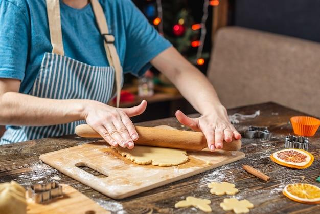 A dona de casa jovem faz massa para cozinhar biscoitos de gengibre festivos