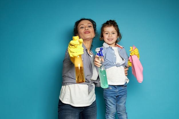 A dona de casa linda dirige sprays de limpeza como se disparasse de uma pistola ao lado de sua filha contra o azul com espaço de cópia