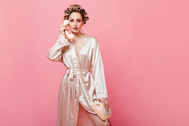 A dona de casa loira com um robe de seda olhando para a frente e segurando um telefone fixo