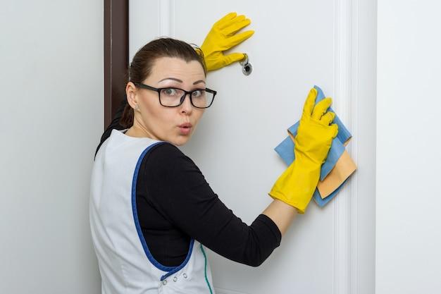 A dona de casa mulher olha no olho mágico da porta da frente