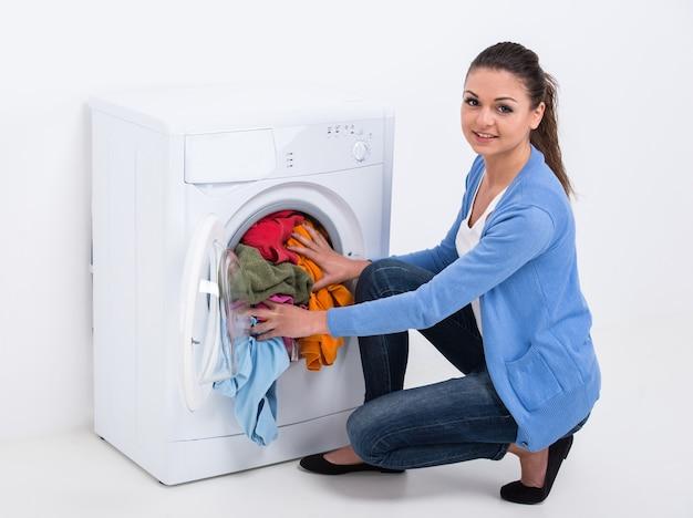A dona de casa nova está lavando roupa com máquina de lavar roupa.