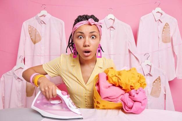 A dona de casa olha surpreendentemente segura a cesta de roupa suja e o ferro elétrico tem muitos postos de trabalho doméstico perto da tábua de passar roupa usa bandana