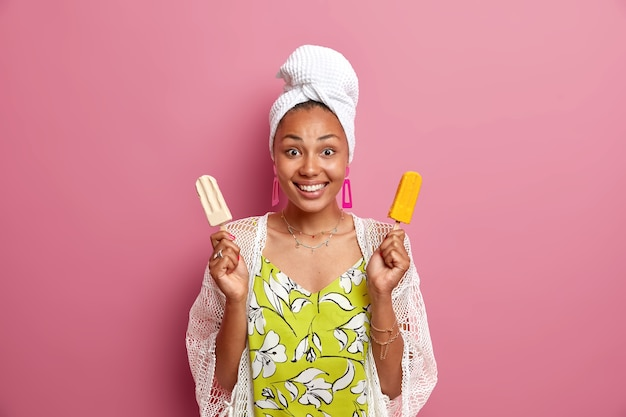 A dona de casa positiva sorri agradavelmente segura um delicioso sorvete em palitos, come uma refeição pouco saudável, tem uma pele bem cuidada, usa roupas domésticas, desfruta de uma deliciosa sobremesa de verão isolada sobre uma parede rosa