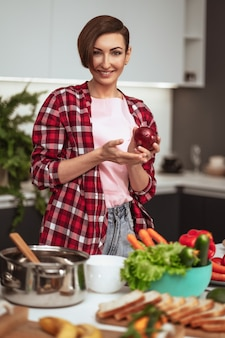 A dona de casa prepara o jantar para a família escolhendo uma verdura segurando uma cebola roxa nas mãos em pé