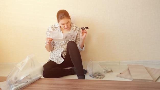 A dona de casa séria se senta no chão e lê a diretiva olhando para os fechos de móveis do armário no espaço da cópia da cozinha do apartamento