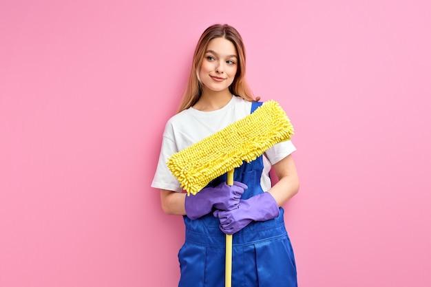 A dona de casa sorridente e de bom humor segurando o equipamento de limpeza, pano no chão, vestindo macacão azul
