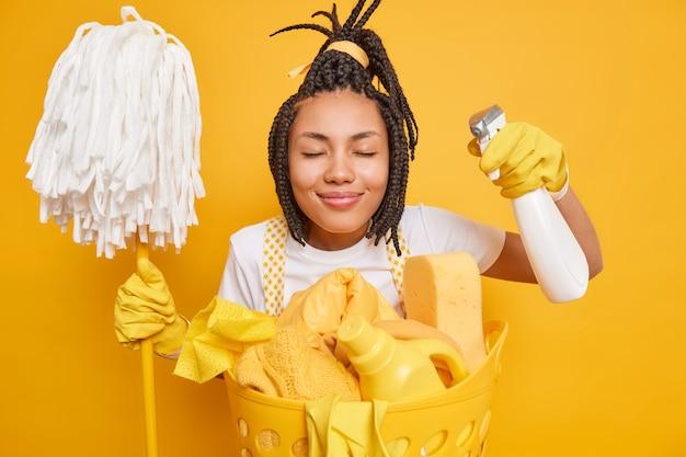 A dona de casa trabalhadora fecha os olhos sorri agradavelmente gosta de limpar