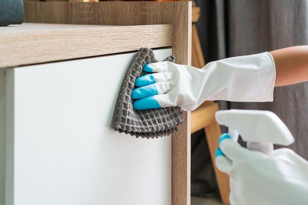 A dona de casa usa uma luva protetora de borracha com pano de microfibra e detergente para limpar a superfície de um armário na sala de estar