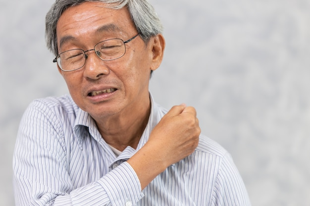A dor traseira asiática do pescoço e do ombro das pessoas idosas usando a mão para massagear e fricciona a vista dianteira.