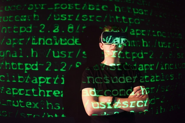 A dupla exposição de um homem caucasiano e um fone de ouvido de realidade virtual vr é presumivelmente um jogador ou um hacker quebrando o código em uma rede ou servidor seguro, com linhas de código em verde