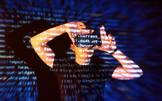 A dupla exposição de um homem caucasiano e um fone de ouvido de realidade virtual vr é presumivelmente um jogador ou um hacker quebrando o código em uma rede ou servidor seguro, com linhas de código