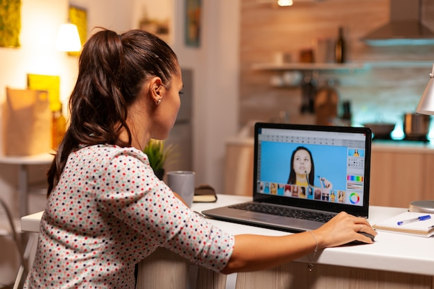 A editora digital feminina trabalha em um software de edição de fotos em seu computador pessoal durante a noite. fotógrafo fazendo software de pós-produção e laptop de desempenho, artista, ocupação, tela, gráfico.