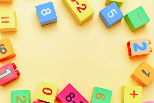 A educação colorida da criança da criança brinca cubos com teste padrão dos números da matemática no amarelo. postura plana com espaço de cópia.
