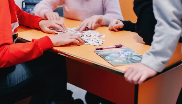 A educação dos alunos joga cartas com imagens em inglês e números