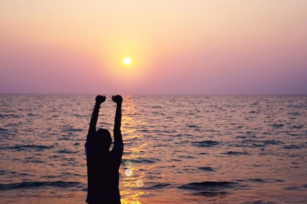 A elevação do homem entrega até o conceito da liberdade do céu com céu azul e fundo da praia do verão.