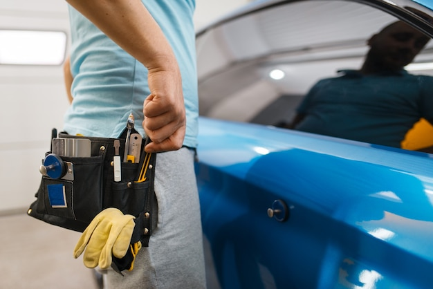 A embalagem de carro masculino com cinto de ferramentas instala uma película protetora de vinil ou filme na embalagem do veículo. trabalhador faz detalhamento de automóveis. revestimento de proteção de pintura automotiva, ajuste profissional
