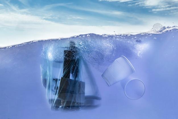 A embalagem de plástico com resíduos de lixo dentro flutua na linha subaquática de água do oceano, problema de ambiente de despejo