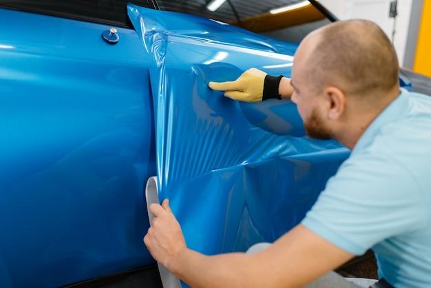A embalagem do carro instala uma película protetora de vinil ou filme na porta do veículo. trabalhador faz detalhamento de automóveis. proteção de pintura automotiva, ajuste profissional