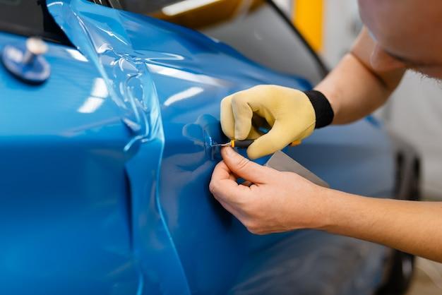 A embalagem do carro instala uma película protetora de vinil ou filme na porta do veículo. trabalhador faz detalhamento de automóveis