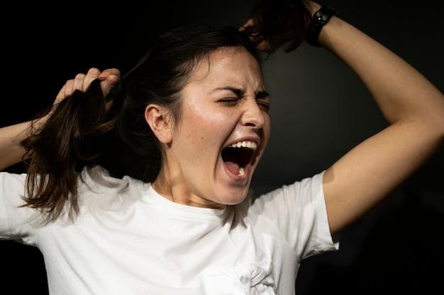 A emoção do ódio, raiva, agressão. a garota em um fundo escuro rasga o cabelo e grita. situação estressante, genve no rosto, expressões faciais brilhantes.