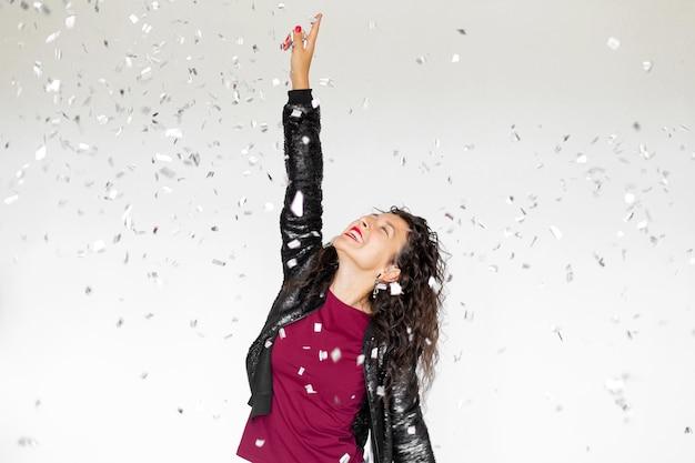 A emoção do sucesso. feliz garota morena sexy está gostando de comemorar com confete em um fundo branco.