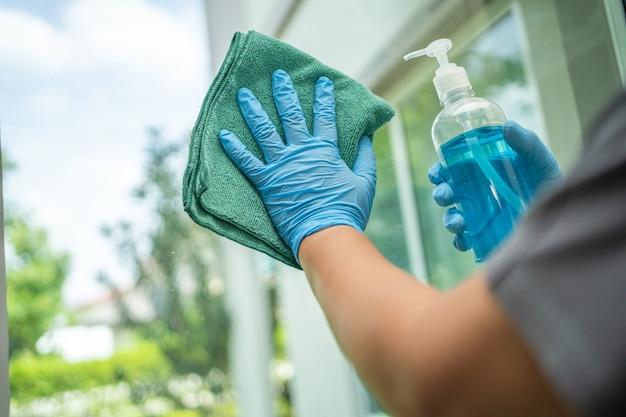 A empregada da limpeza limpa e lava o vidro na viúva em casa.