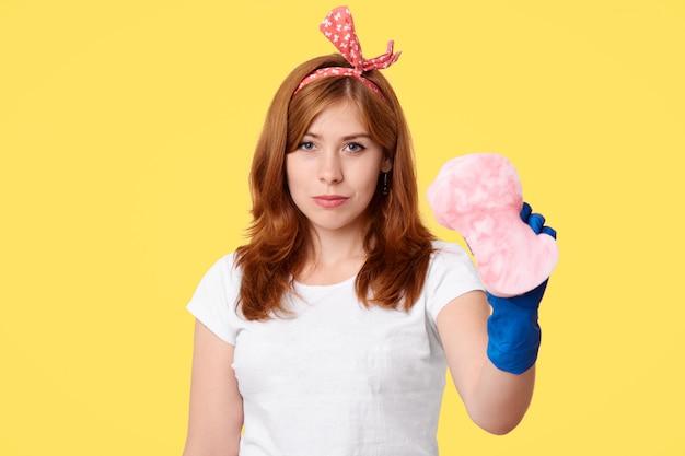 A empregada doméstica bonita trabalha duro segura a esponja, removendo a poeira em toda parte
