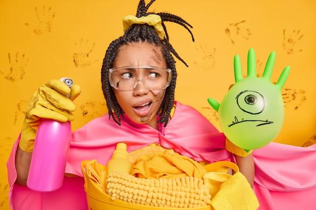 A empregada, intrigada, ocupada, de pele escura, trabalha muito em casa, vestida com uma fantasia de super-heroína, e segura o detergente de limpeza isolado sobre a parede amarela