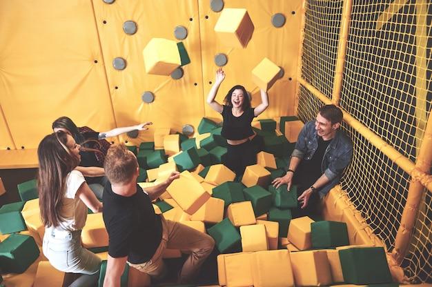 A empresa é uma jovem que se diverte com blocos macios em um parque infantil em um centro de trampolim.