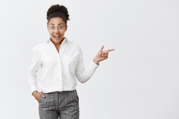 A empresária bonita de pele escura não consegue acreditar que viu uma empresária famosa durante a reunião, de óculos da moda e terno formal sobre a parede cinza, apontando para a direita com o dedo indicador