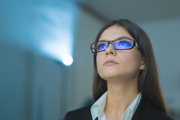 A empresária de óculos no fundo do projetor