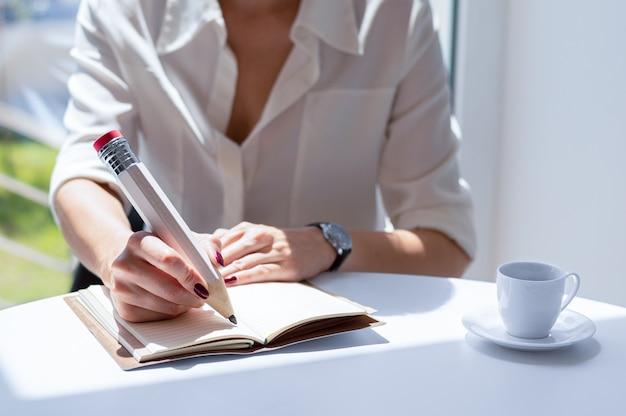 A empresária escreve em um caderno com um lápis grande.