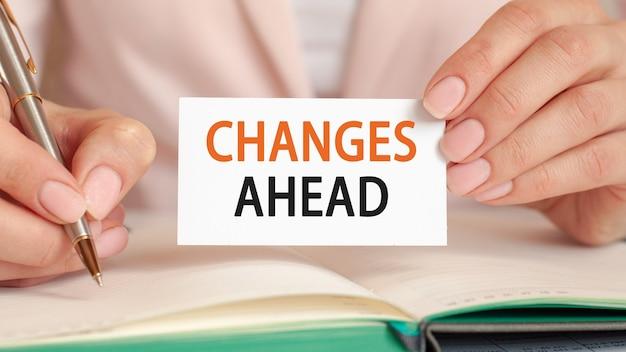 A empresária escreve em um caderno com uma caneta de prata e um cartão de espera de mão com o texto: mudanças à frente. conceito de negócios e educação.