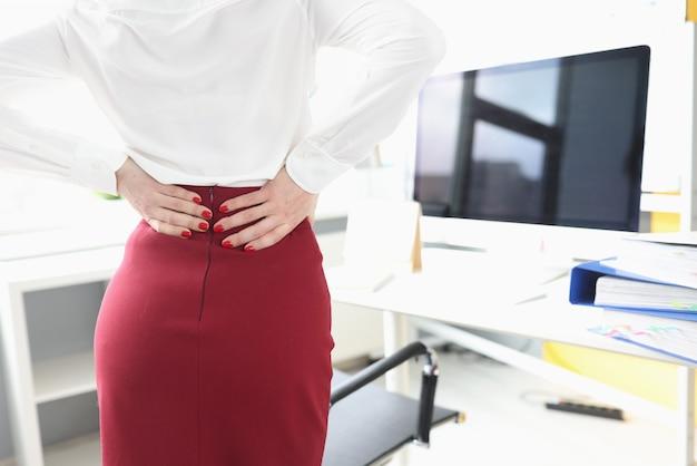 A empresária está de pé ao lado de sua mesa e sente dores nas costas