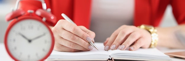 A empresária faz anotações em documentos; há um despertador ao lado