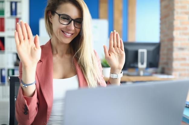 A empresária no escritório levantou duas mãos