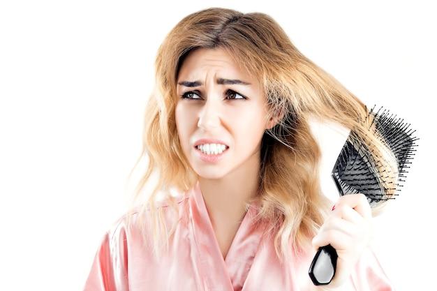 A encantadora garota foi fisgada por um fio de cabelo como pente e fez uma careta de dor.