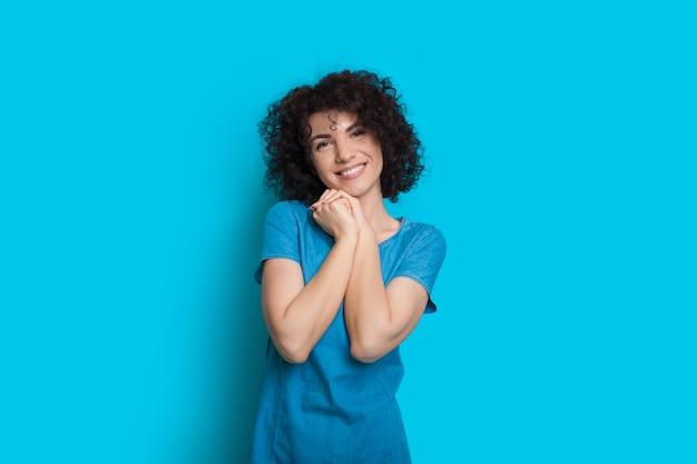 A encantadora senhora caucasiana com cabelo preto encaracolado está olhando para a câmera e sorrindo alegremente
