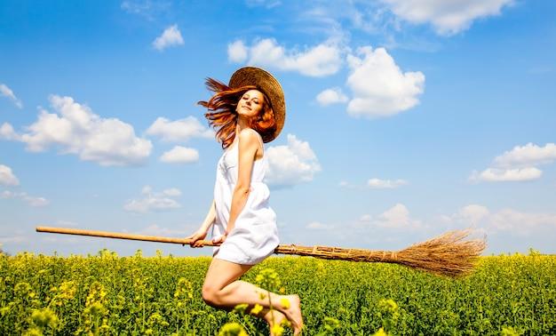 A enchantress do redhead voa sobre o campo da colza da mola na vassoura.