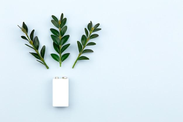 A energia de eco ou a ilustração das energias verdes com uma bateria e os ramos brancos saem em um fundo claro com o espaço da cópia para o texto.