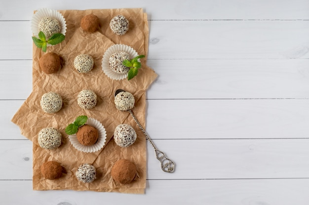 A energia morde com pó de cacau, sementes de gergelim e flocos de coco na mesa de madeira branca, vista superior. espaço para texto