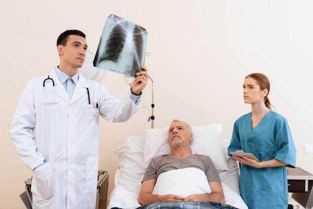 A enfermeira e o velho também examinam a imagem.