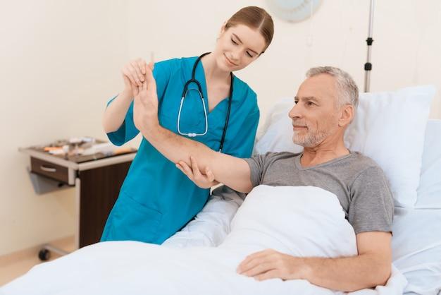 A enfermeira está ao lado do velho e examina a mão dele.