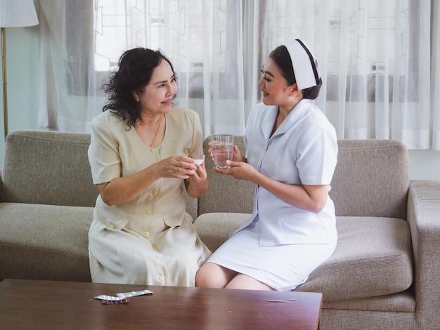 A enfermeira está cuidando do idoso com felicidade