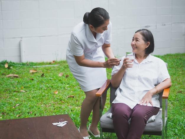 A enfermeira está cuidando dos idosos com felicidade, a mulher mais idosa toma drogas com água