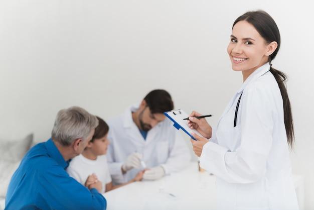 A enfermeira está registrando resultados da amostragem de sangue.