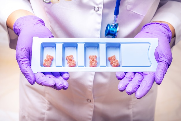 A enfermeira holdinf conteiner com vitaminas de crianças